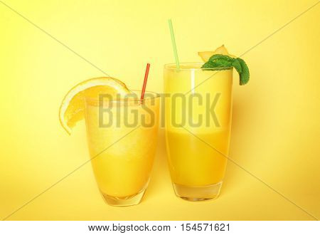 Carambola and orange smoothies on color background