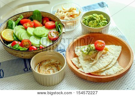 Healthy meal with organic tomato green salad, naan bread and dessert