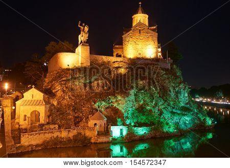 Metekhi orthodox monastery church at sunset and Statue of King Vakhtang Gorgasali. Touristic landmark in Tbilisi Georgia