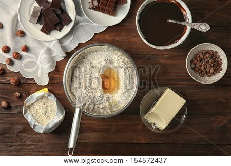 Ingredients for making chocolate cake on wooden background, top view