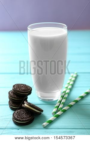 Tasty chocolate cookies, glass of milk and straws on wooden table