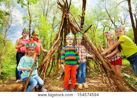 Portrait of happy kids in Injun's costumes, building wigwam of branches in the forest