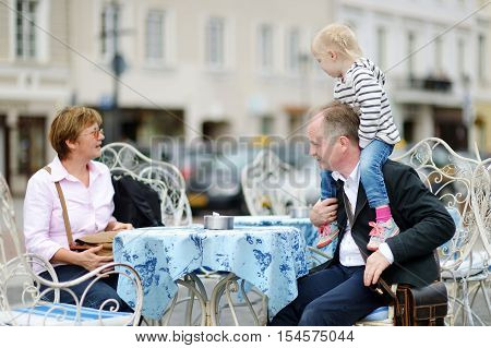 Grandparents and their grandchild at summer cafe on beautiful sunny day