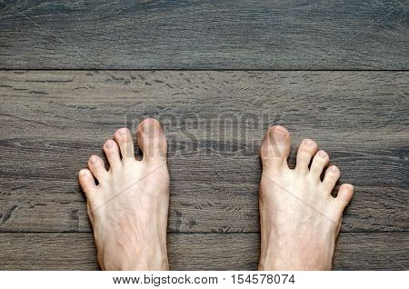 Bare male feet on the wooden floor closeup