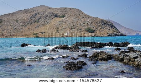 Rocky coast on the background of mountains. lear sunny. the waves beating against the volcanic rock