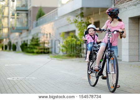 Young mother and her cute little toddler daughter in a child seat getting ready to ride a bicycle