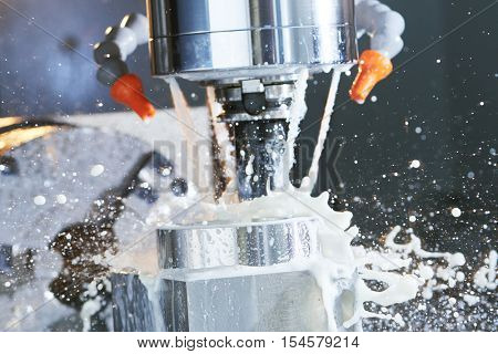 Milling metalworking process. Industrial precision CNC metal machining by vertical cutting mill with coolant