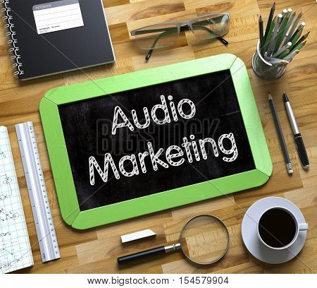 Audio Marketing Handwritten on Green Chalkboard. Top View Composition with Small Chalkboard on Working Table with Office Supplies Around. Audio Marketing - Text on Small Chalkboard.3d Rendering.