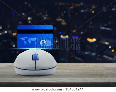 Wireless computer mouse with blue credit card on wooden table over blur light city tower Online e-payment concept