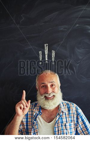 Old bearded man is pointing up against blackboard with exclamation mark chalk inscription