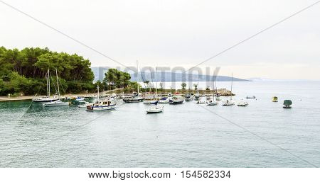 The port on the old town of Krk in Croatia county Primorje-Gorski Kotar. A view of the Adriatic sea boats docked the coast of the island Veglia and part of the city walls.