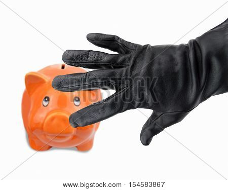 black gloved hand of a thief stealing a piggy bank pig shaped orange and white background
