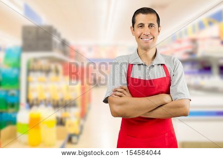 portrait of smiling shopman standing and looking at the supermarket with crossing arms