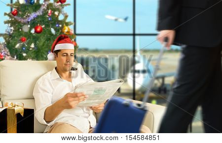 Business man with santa hat waiting for his flight at the VIP area of the airport