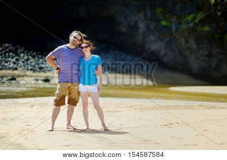 Young couple enjoying tropical vacations on Hanakapiai beach