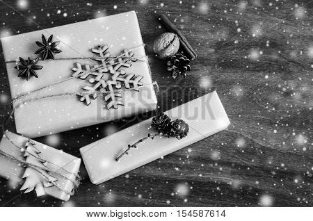 Kraft Boxes with Gifts Decorated with Wooden Snowflake Christmas Tree and Jute on Wooden Background. Vintage Image with Drawn Snowfall. Christmas in Rustic Style. View from above with copy space.