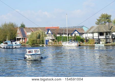 Wroxham Norfolk United Kingdom - October 25 2016: Pleasure boats on River Yare centre for tourism on Norfolk Broads with houses in background