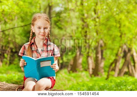 Portrait of diligent schoolgirl reading a book, sitting on a log in summer park