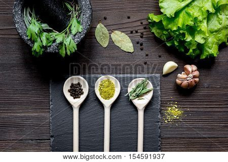 spices for cooking and fresh salad with pounder on wooden table top view