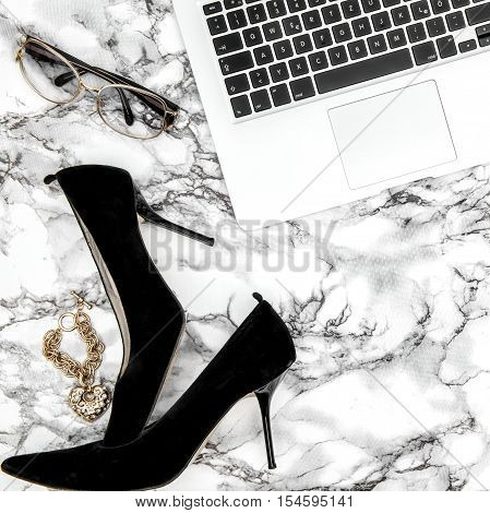 Feminine accessories und notebook on marble table background. Fashion flat lay for blogger social media Instagram style