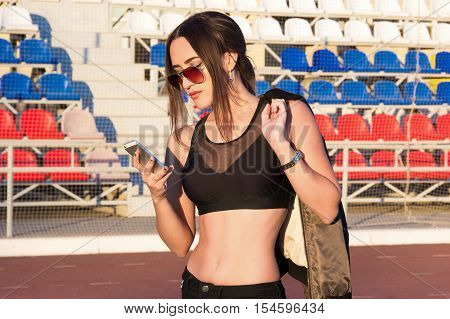 Beautiful girl texting on a smart phone in the stadium. Young athletic woman in a short tank top and sunglasses