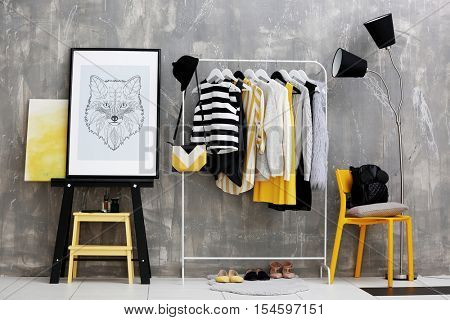 Fashionable clothes hanging on rack at modern dressing room