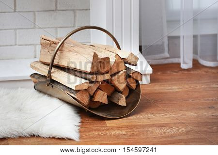 Basket with firewood in living room, close up view