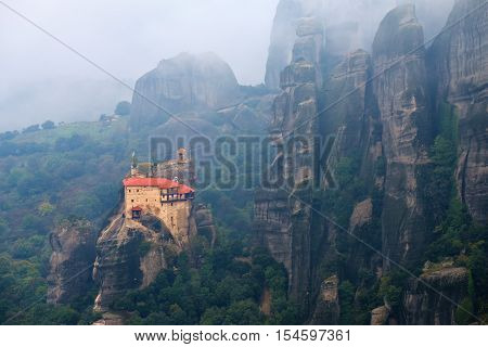 Meteora monasteries. View on the Holy Monastery of St Nikolaos Anapafsas placed on the edge of high rock and covered morning mist Kastraki Greece