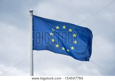The flag of the European Union fluttering on wind against the background of gray clouds.