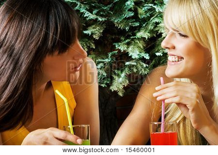 women drinking juice and talking,  outdoor daylight