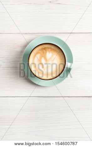 Cappuccino with frothy foam, blue coffee cup top view closeup on white wood background. Cafe and bar, barista art concept. Vertical image