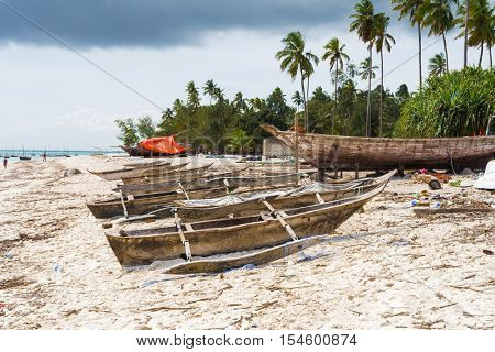old wooden fishing boat with oar on african beach near a village
