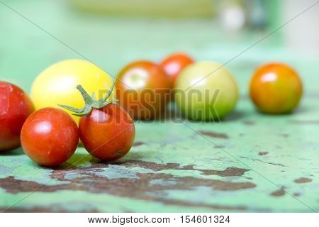 Tomato cherries on a old green wooden surface.