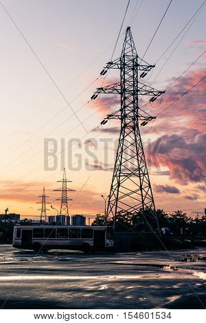 Tower of power lines in the suburbs in the evening after the rain against the backdrop of pink clouds