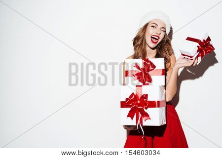 Excited happy woman in red santa claus outfit holding stack presents isolated on the white background