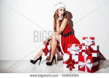 Happy lovely young woman in santa claus costume with present boxes sitting on the floor isolated on the white background