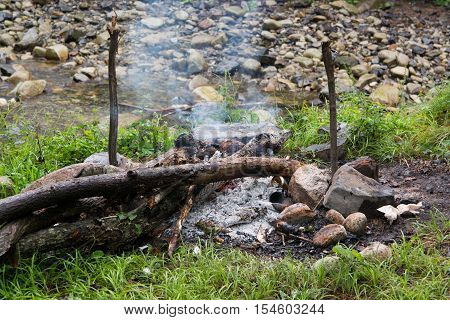 Firewood and embers in a fading bonfire. Smoke rises on a riverbank background.
