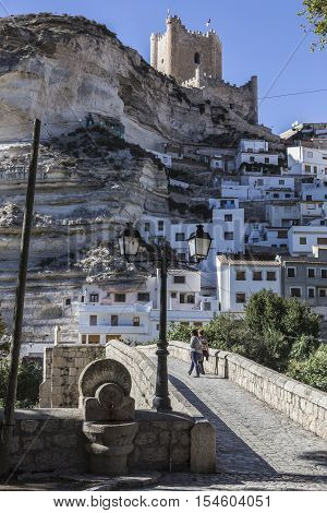 Alcala del Jucar Spain - October 29 2016: Roman bridge located in the central part of the town to its passage by the river Jucar at the top of mountain limestone is situated castle of Almohad origin of the century XII take in Alcala of the Jucar Albacete