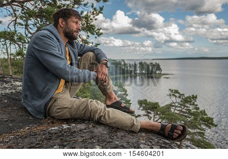 Handsome man is sitting on the rock and looking into the distance