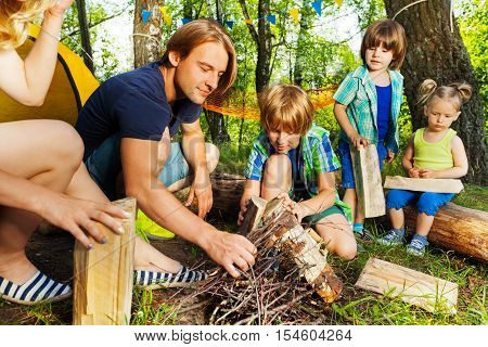 Portrait of young father teaching his three age-diverse kids making a camp fire in the forest