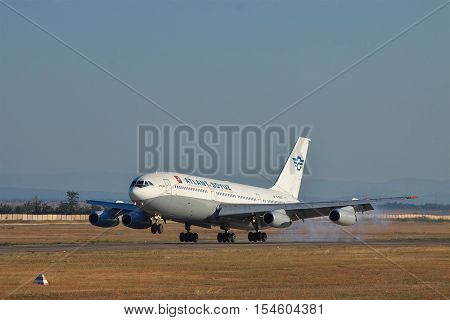 Simferopol Ukraine - September 12 2010: Ilyushin Il-86 passenger plane landing and touchdown on the runway with mountains on the background