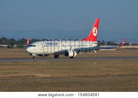 Simferopol Ukraine - September 12 2010: Turkish Airlines Boeing 737NG reversing the engine thrust after the landing on the runway on sunset