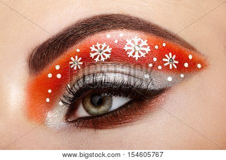 Eye girl makeover snowflakes. Winter christmas makeup. Beauty fashion. Eyelashes. Cosmetic Eyeshadow. Makeup detail. Creative woman holiday make-up