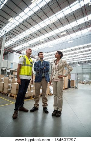 Warehouse managers discussing with the worker in warehouse
