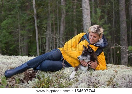 Woman-tourist is laying on the forest meadow with a dog