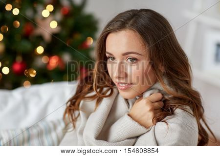 x-mas, winter holidays and people concept - happy young woman with plaid over christmas tree at home