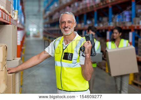 Portrait of smiling warehouse worker scanning box in warehouse