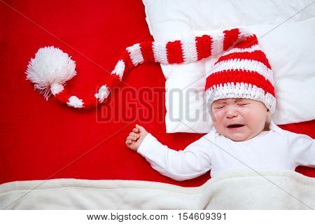 Sleepy baby on red blanket in knitted hat. Cute child crying in christmas cap