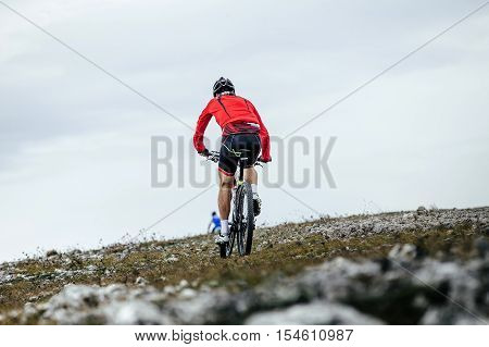 riders on sport bikes riding down mountain slope. competitions on mountainbike