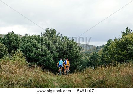 two riders on sports mountainbike ride mountain forests. Cycling competition